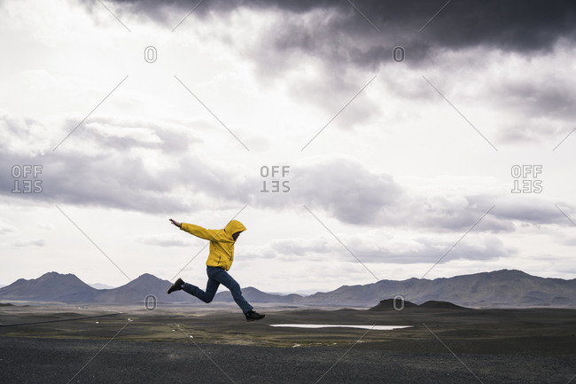 Mature man jumping for joy in the Highland Region- Iceland