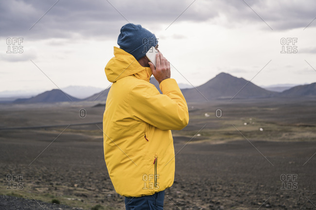 Mature man talking on his smartphone in the Icelandic highlands