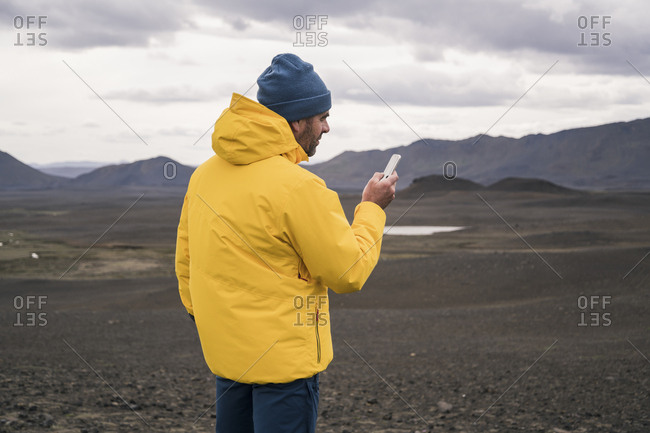 Mature man using smartphone in the Icelandic highlands