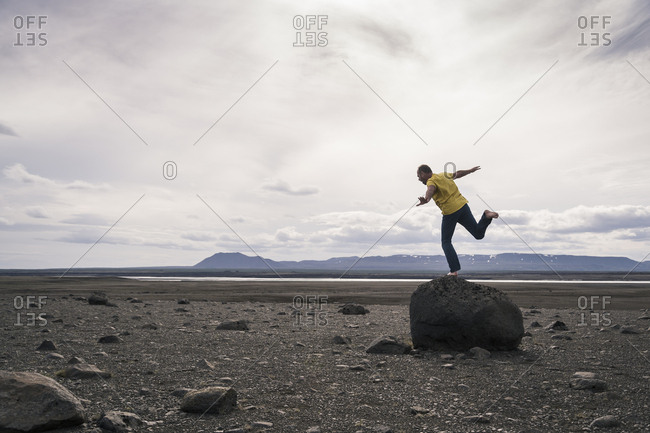 Mature man balancing on one leg on a rock in the volcanic highlands of Iceland