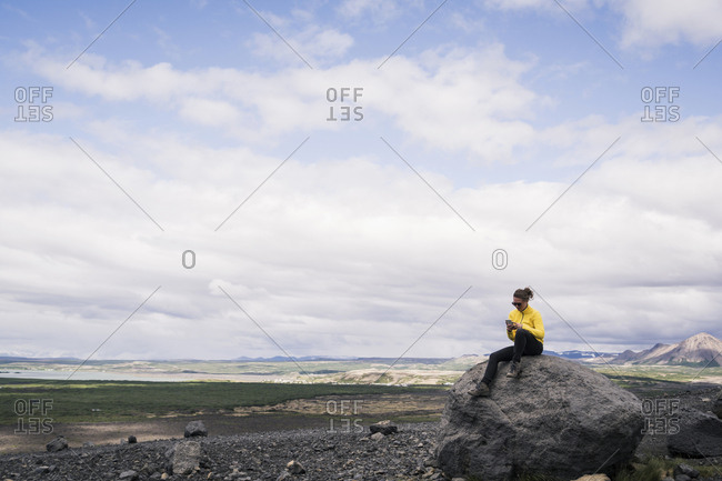 Young woman sitting on rock at Myvatn- Iceland- using smartphone