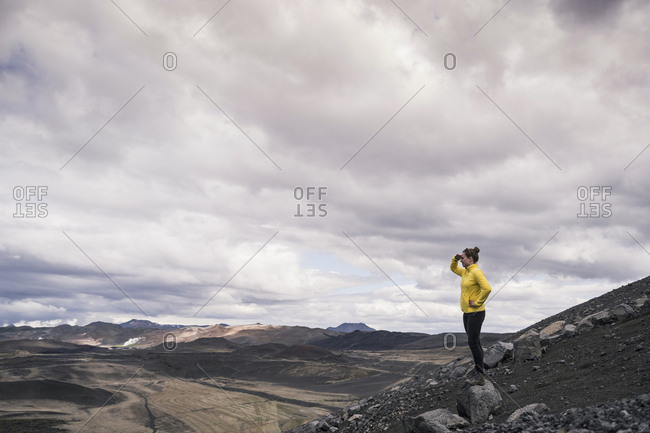 Young woman standing on Hverfjall crater near Myvatn- Iceland- looking at view