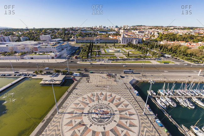 March 27, 2019: Portugal- Lisbon- Belem- High angle view of compass rose and map mosaic near marina- Jeronimos Monastery in background