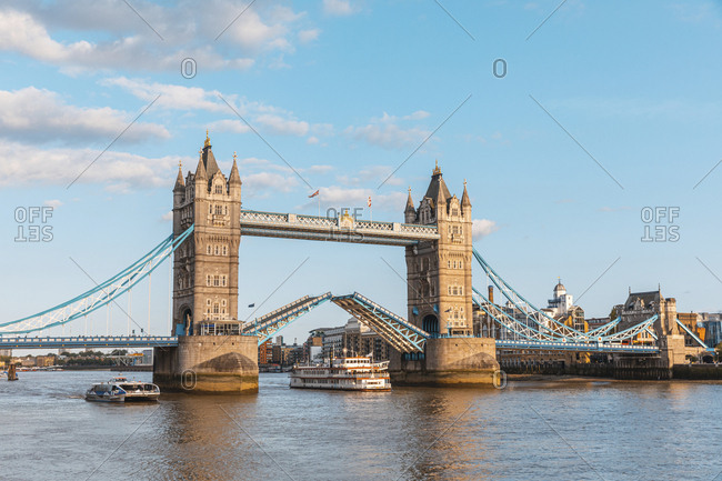 Paddle steamer boat moving under lifted Tower Bridge- London- England- UK