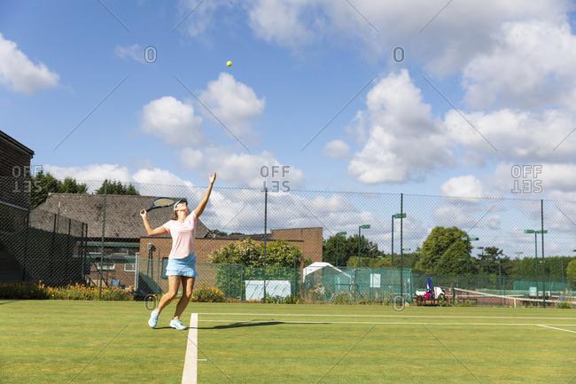 Mature woman serving during a tennis match on grass court