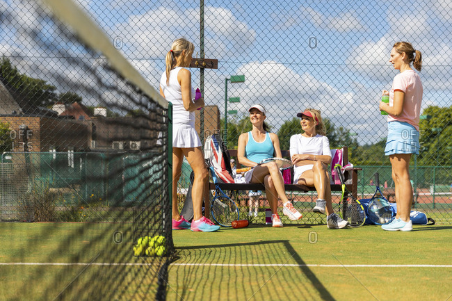 Mature women at tennis club taking a break from playing