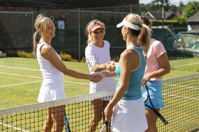 Mature women finishing tennis match on grass court shaking hands