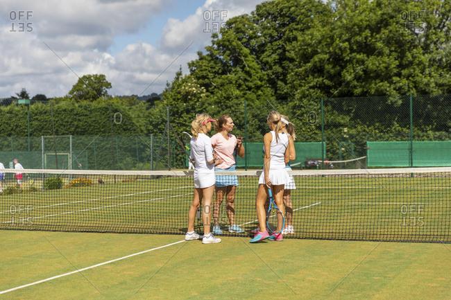 Mature women finishing tennis match on grass court