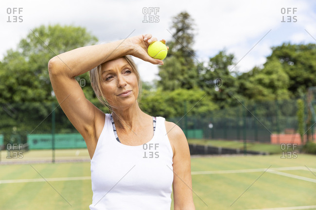 Tired female tennis player taking a break on grass court at tennis club