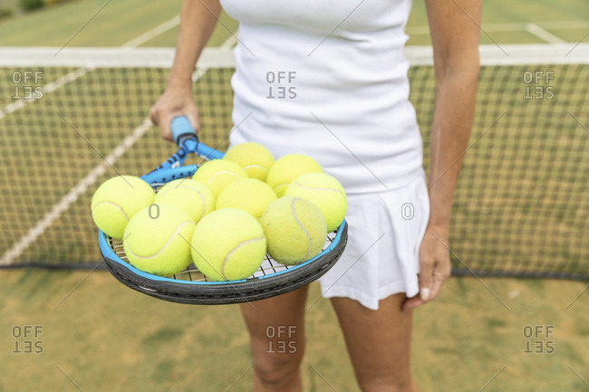 Female tennis player holding a tennis racket with balls on grass court