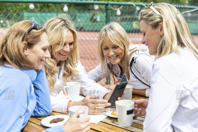Group of women enjoying tea and coffee with biscuits and sharing smartphone at tennis club after a match