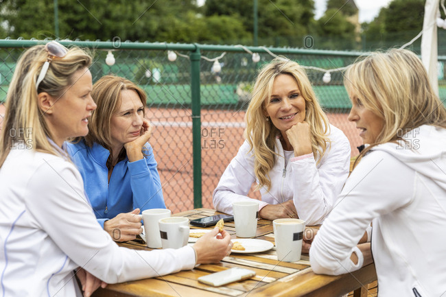 Group of women talking in a cafe at tennis club after a match