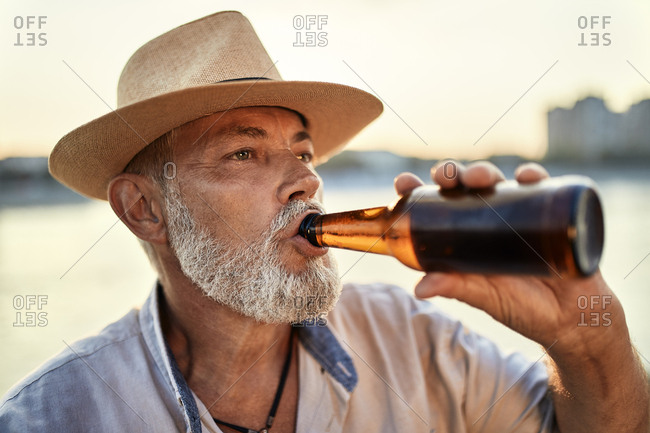 Senior man drinking a beer at the riverside at sunset