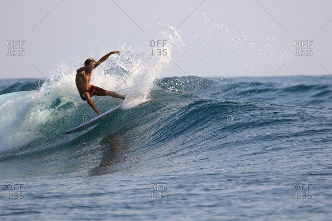 A male surfer rides a wave in Indonesia