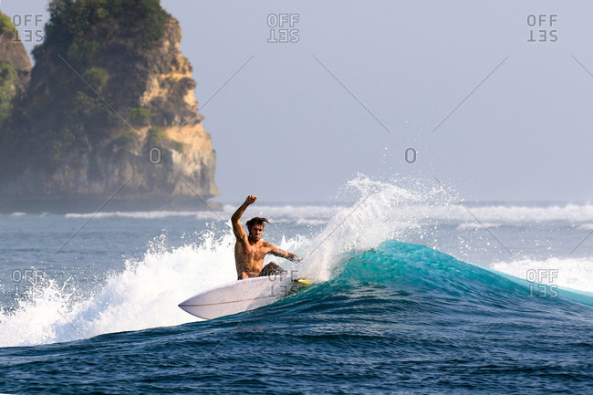Male surfer riding a wave in Indonesia