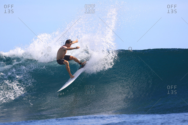 A male surfer riding a wave in Indonesia