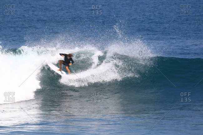 A surfer rides a curling wave in Indonesia