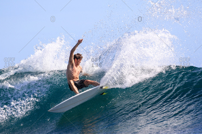 Man riding a wave on a surfboard in Indonesia