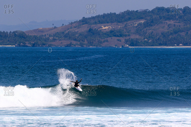 A surfer riding a wave in the distance in Indonesia