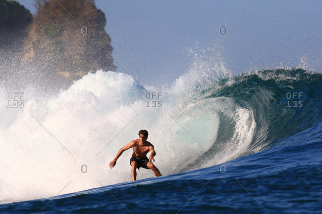 Low angle view of a surfer riding a wave in Indonesia