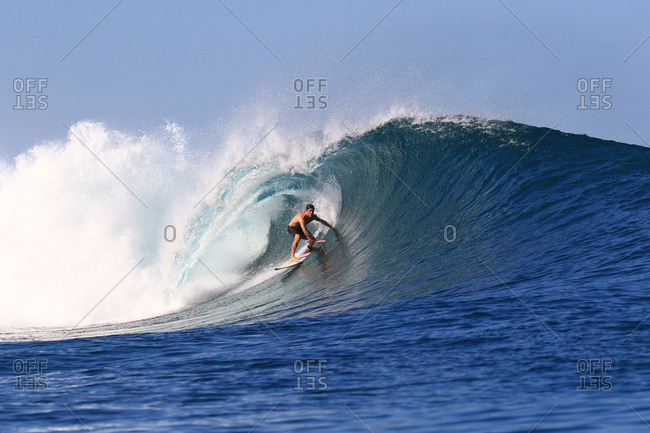 A surfer rides a large perfect barreling wave in Indonesia