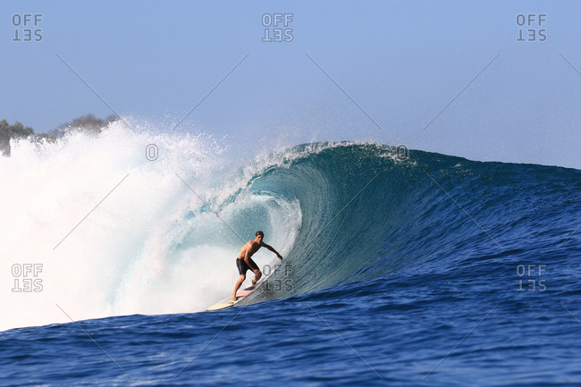 A surfer rides a large barreling wave in Indonesia
