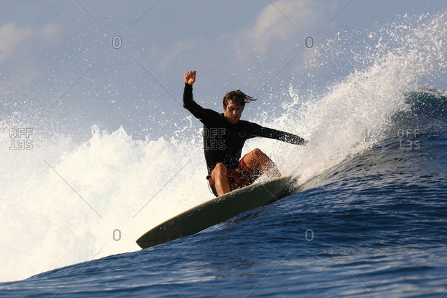 A surfer does a turn on e wave in Indonesia