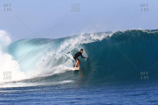 A surfer rides a big barreling wave in Indonesia