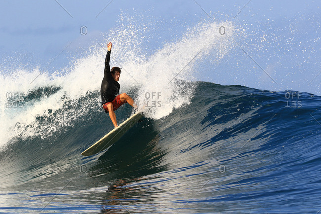 Male surfer does a turn on wave in Indonesia