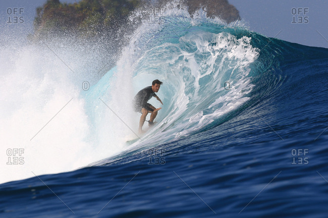 A surfer riding inside a big barrel wave in Indonesia