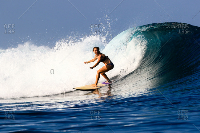 A female surfer rides a wave in Indonesia