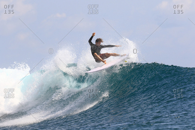 A surfer splashing while doing a turn on wave in Indonesia