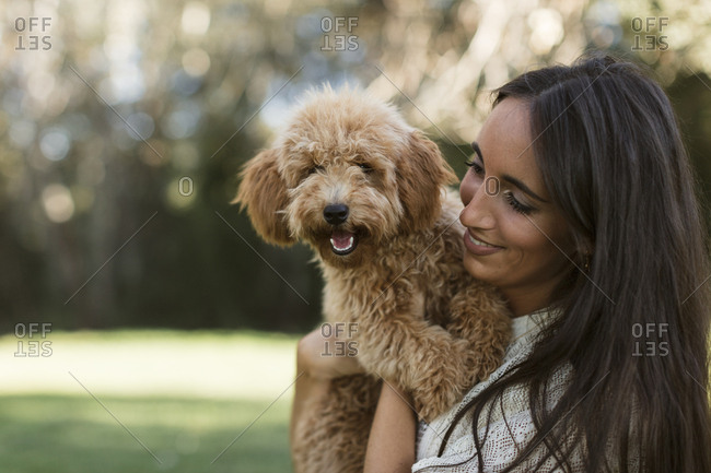 Beautiful Indian woman holding a golden-doodle puppy