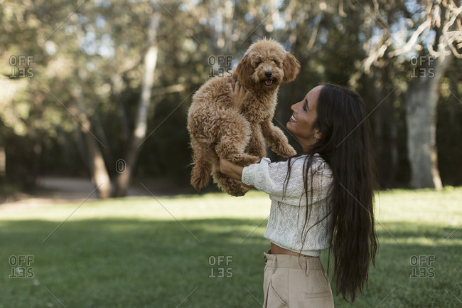 Beautiful Indian woman holding a golden-doodle puppy up in the air