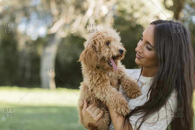 Indian woman holding a golden-doodle puppy