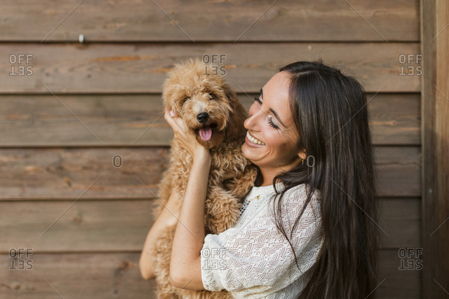 Beautiful Indian woman cuddling with a golden-doodle puppy