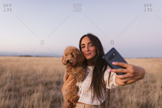 Beautiful Indian woman taking selfie while holding a golden-doodle puppy