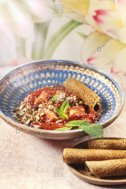 Crepe dish with tomato sauce and nuts
