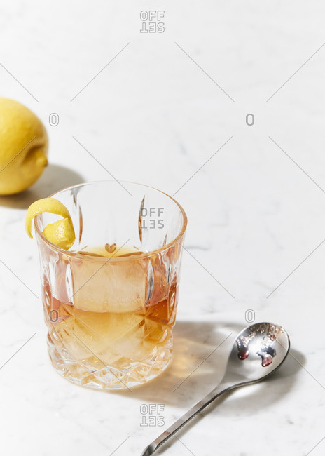 Classic old fashioned in a cocktail glass on marble surface by lemon