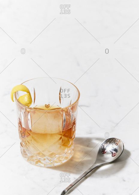 Classic old fashioned in a cocktail glass on marble surface
