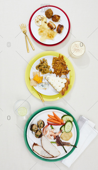 Stoplight arrangement of three gourmet holiday dishes with drinks and napkin