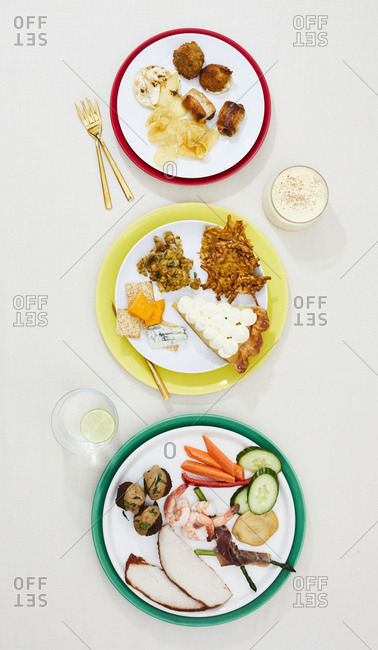 Stoplight arrangement of three gourmet holiday dishes with drinks