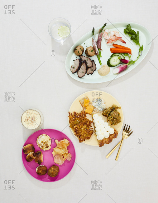 Overhead view of three course gourmet dishes with drinks
