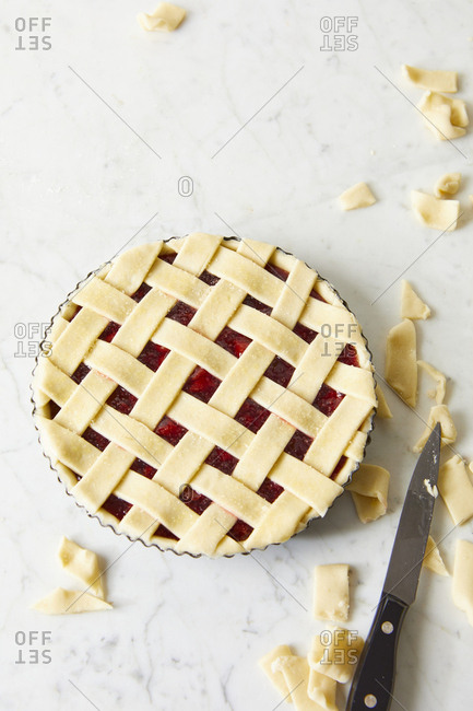 Homemade cherry pie being prepared on marble surface