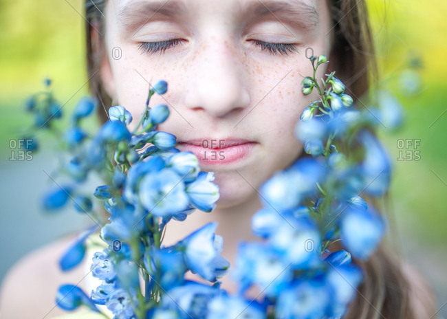 Girl with freckles smelling blue flowers