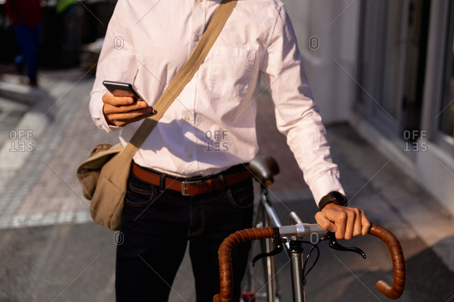 Young professional man using smartphone and holding a bike