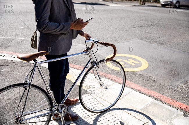 Young professional man on a bike using smartphone and holding a bike on the street