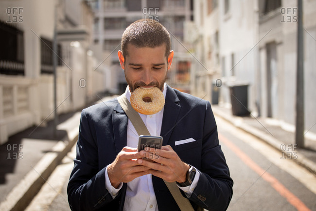 Young professional man eating a doughnut and using smartphone on the street