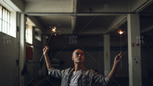 Young man holding sparkles inside an empty warehouse