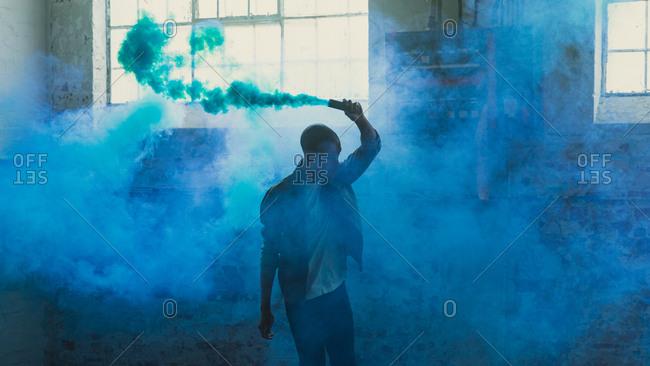 Young man holding a smoke maker inside an empty warehouse